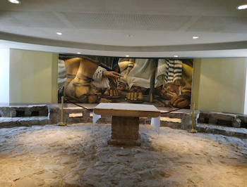 "Fig. 3. Encounter Chapel at the modern prayer house Duc In Altum. The chapel was positioned on top of 1st century port pavement. The interior is modeled after Magdala's synagogue (note the stone benches which reconstruct similar benches discovered in the ""vestibule room"" of the synagogue). Photograph by the author, 2018."